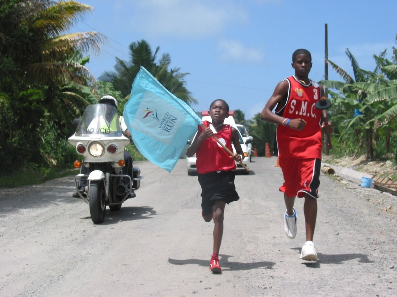 St. Lucia sprinters with flag, police escort