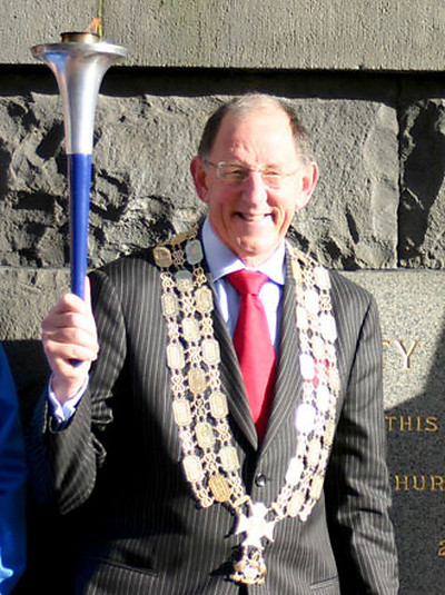 The Mayor of Auckland, Dick Hubbard holds the World Harmony Run torch