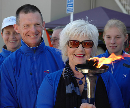 Nita Knight holds the World Harmony Run torch surrounded by members of the Harmony Run team. title=